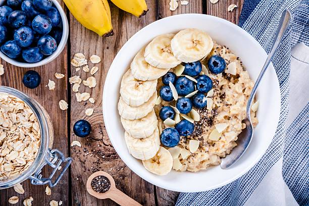 Breakfast: oatmeal with bananas, blueberries, chia seeds and almonds Breakfast: oatmeal with bananas, blueberries, chia seeds and almonds. Top view oatmeal stock pictures, royalty-free photos & images