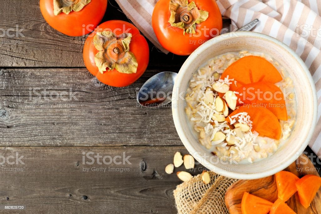 Breakfast oatmeal with persimmons overhead on wood stock photo