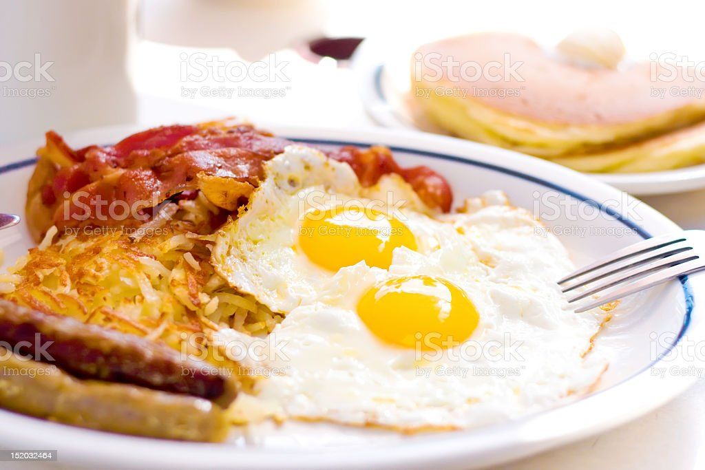 Breakfast of 2 eggs, sausage, hashbrowns, bacon and pancakes royalty-free stock photo