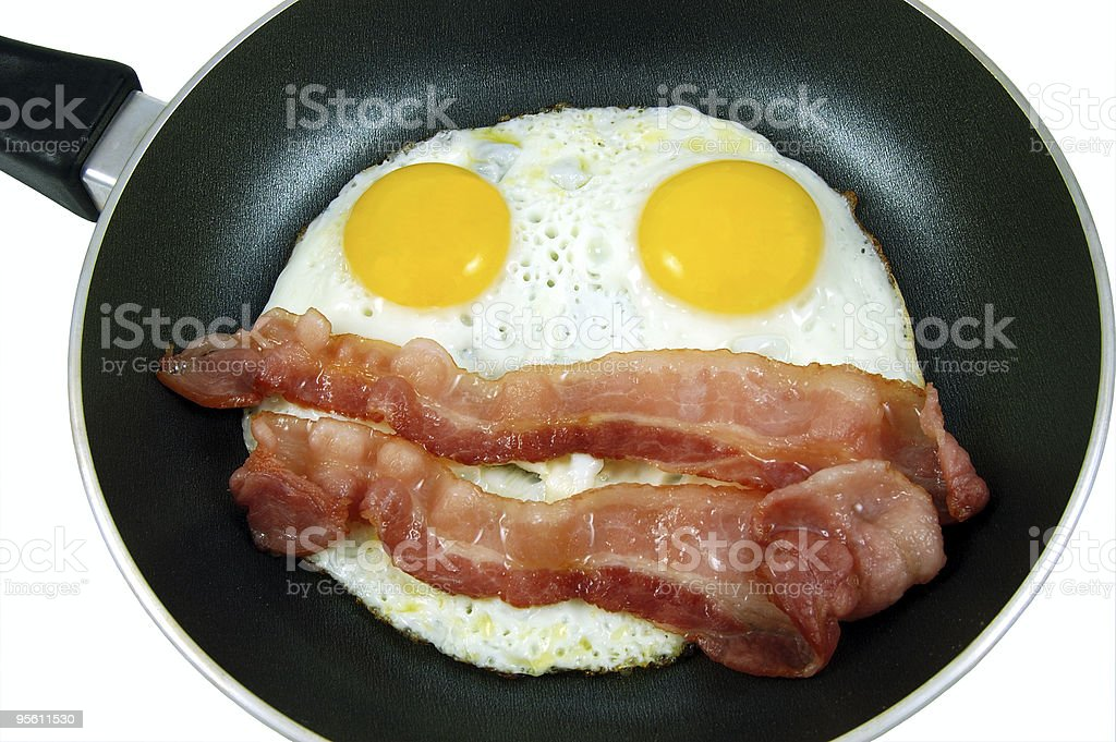 A breakfast of bacon and eggs frying in a hot skillet stock photo