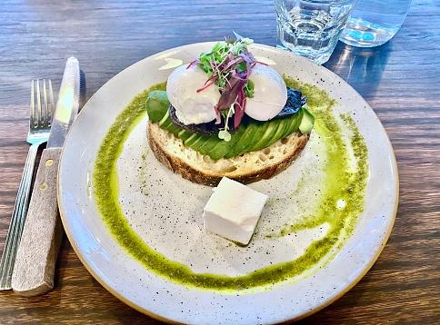 Horizontal close up of breakfast plate with soft poached eggs avocado lemon thyme marinated field mushrooms feta salsa verde and organic sourdough