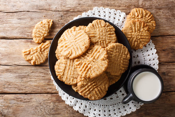 Breakfast of peanuts butter cookies with milk close-up. Horizontal top view stock photo