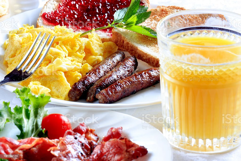 Breakfast of sausage, egg and toast with orange juice stock photo