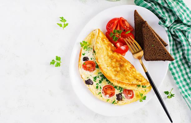 Frühstück. Omelette mit Tomaten, schwarzen Oliven, Hüttenkäse und grünen Kräutern auf weißem Teller.  Frittata - italienischeome. Ansicht von oben – Foto
