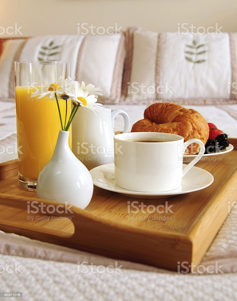 Breakfast on a tray on a bed with white linens royalty-free stock photo