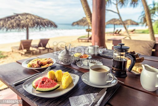 Breakfast on sea beach in Sri Lanka. Table setting with vegan food and coffee in restaurant outdoor. Buffet with exotic fruits on ocean coast. Concept of travel and vacation in tropical resort.