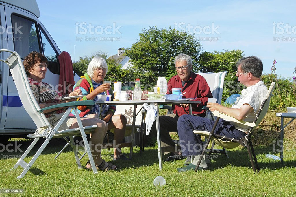 Breakfast on campsite with four seniors and motor home royalty-free stock photo
