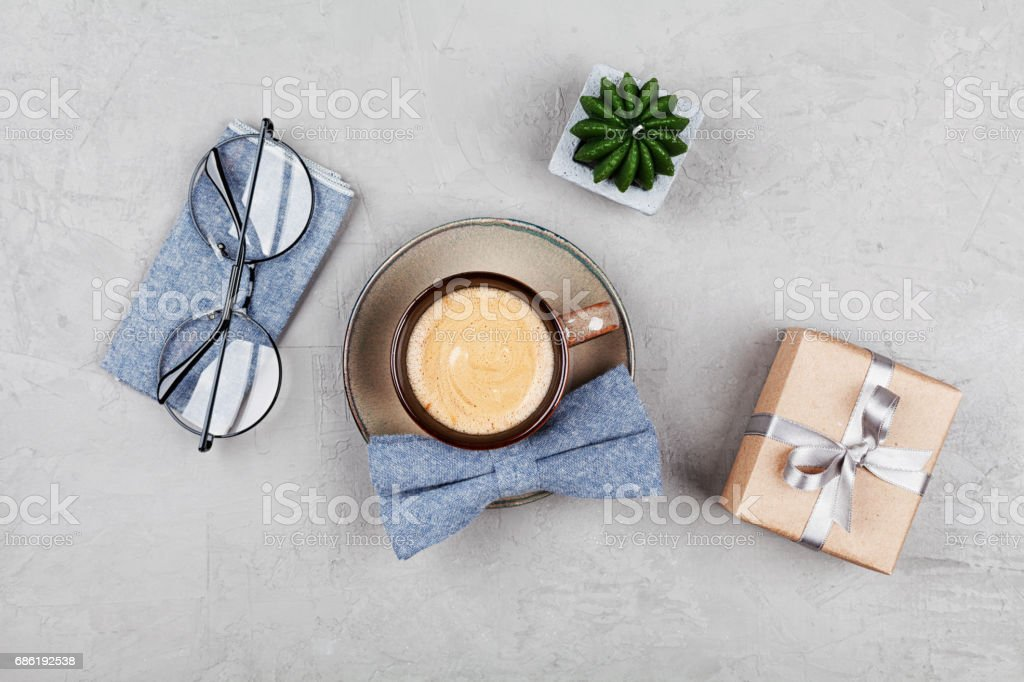 Breakfast on Happy Fathers Day. Morning coffee mug, gift, glasses and bowtie on stone table. Flat lay. stock photo