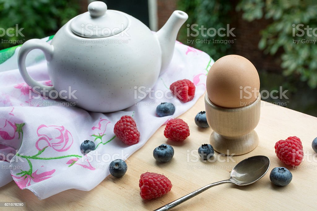 Breakfast on the table with white teapot, egg and berries photo libre de droits