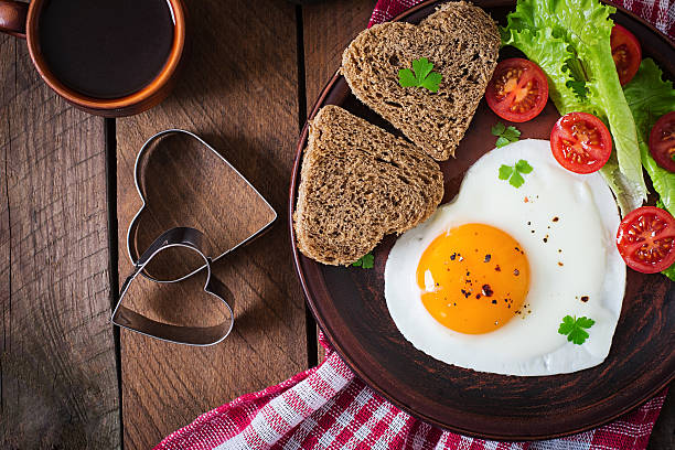 breakfast on valentine's day - fried eggs - fried egg stock photos and pictures