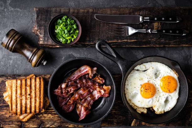 아침 식사 또는 브런치 튀긴 베이컨 그리고 계란 검은 프라이팬에 바 삭 토스트 평면도 - 베이컨 뉴스 사진 이미지