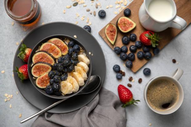 frühstück oder brunch brei hafer mit feigen, heidelbeeren, bananen, kaffee, milch, honig, sirup, kaffee bohnen, erdbeeren - sonntagsbrunch stock-fotos und bilder