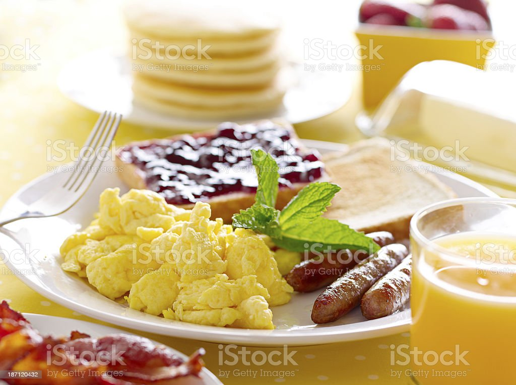 A breakfast plate with scrambled eggs, sausage, and toast stock photo