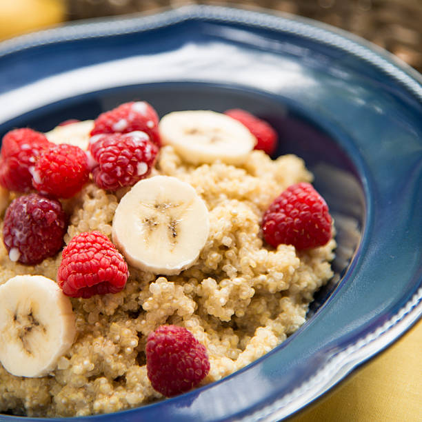 Breakfast Quinoa with Raspberries and Bananas A bowl of quinoa with raspberries and bananas for breakfast. quinoa stock pictures, royalty-free photos & images