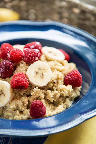 Breakfast Quinoa with Raspberries and Bananas Vertical A bowl of quinoa cereal with raspberries and bananas.Similar Images: quinoa stock pictures, royalty-free photos & images