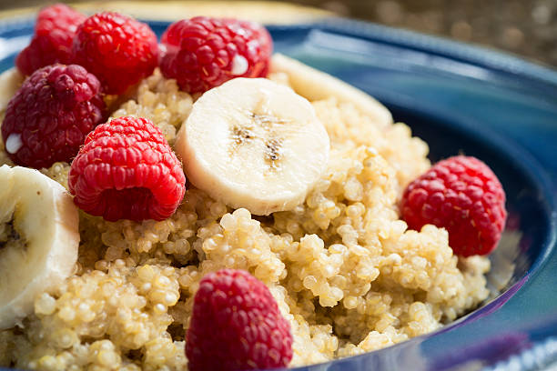 """Breakfast Quinoa with Raspberries, Bananas Horizontal Close-up """"A close-up of a bowl of Quinoa cereal with bananas, raspberries and a splash of milk.  Similar Images:"""" quinoa stock pictures, royalty-free photos & images"""
