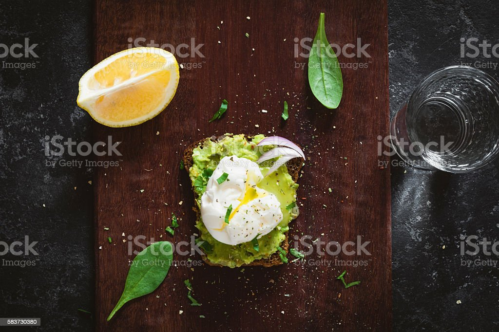 Breakfast sandwich with avocado and poached egg stock photo