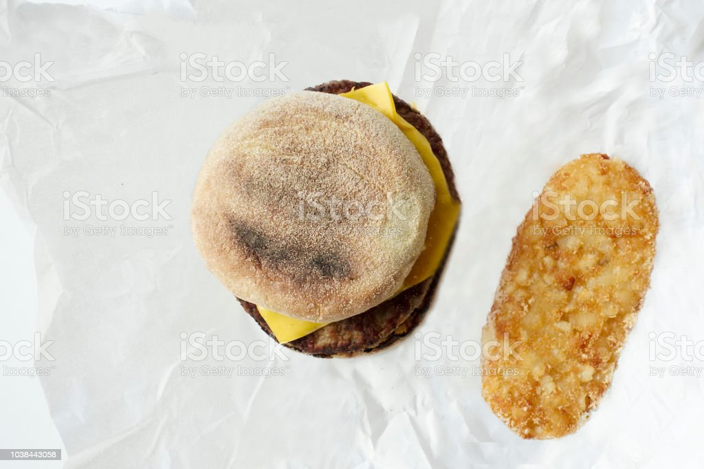 Breakfast sausage burger roll and hash brown view from above on paper sheet stock photo
