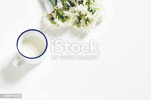 istock Breakfast scene. Spring composition with mug of milk and bouquet of narcissus, daffodil flowers on white wooden table background. Easter concept. Flat lay, top view. Styled stock image. 1090575526