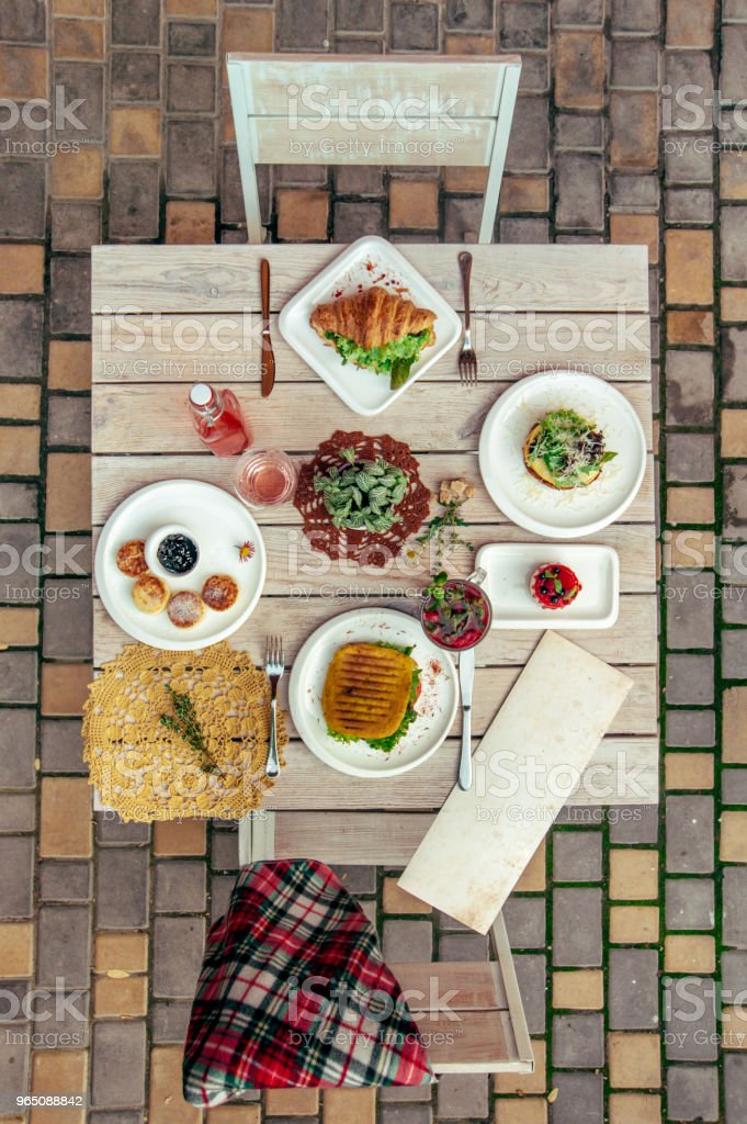 breakfast served cafe table with cheese pancakes, sandwich, croissant and drinks. Top view royalty-free stock photo