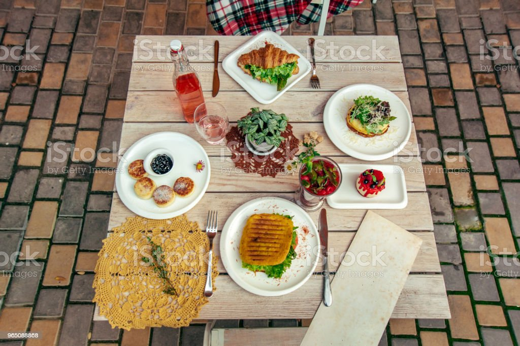 breakfast served cafe table with cheese pancakes, sandwich, croissant and drinks. Top view zbiór zdjęć royalty-free