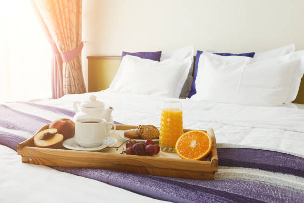 Breakfast served in bed on wooden tray stock photo