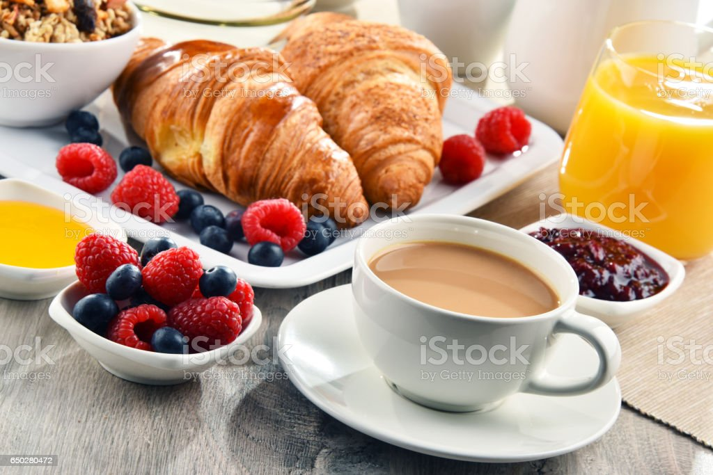 Breakfast served with coffee, juice, croissants and fruits stock photo