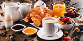 istock Breakfast served with coffee, juice, croissants and fruits 854478938