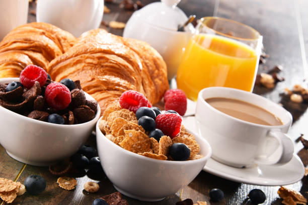 breakfast served with coffee, juice, croissants and fruits - breakfast stock pictures, royalty-free photos & images