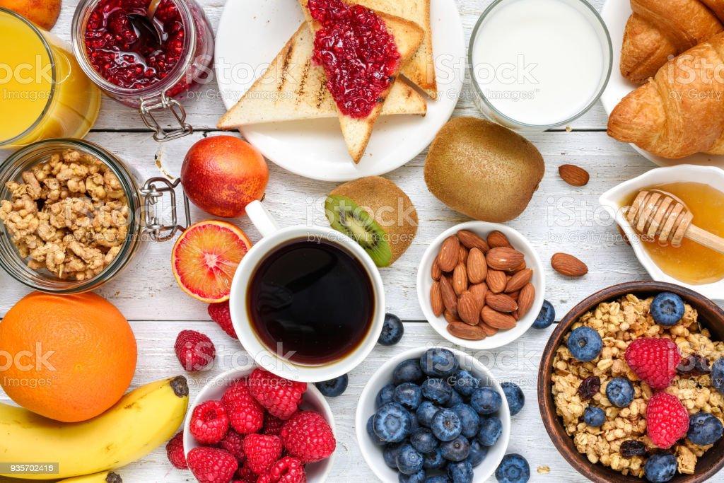 朝食はコーヒー、オレンジ ジュース、トースト、クロワッサン、シリアル、ミルク、ナッツ、果物を提供しています。バランスの取れた食事 ストックフォト