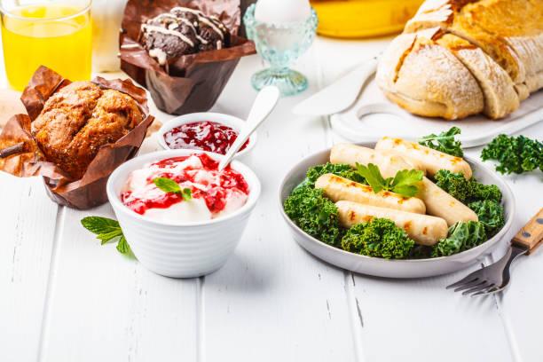 frühstück mit muffins, gegrillte würstchen, saft, frisches brot und parfait auf weißer holztisch. - käse wurst salat stock-fotos und bilder