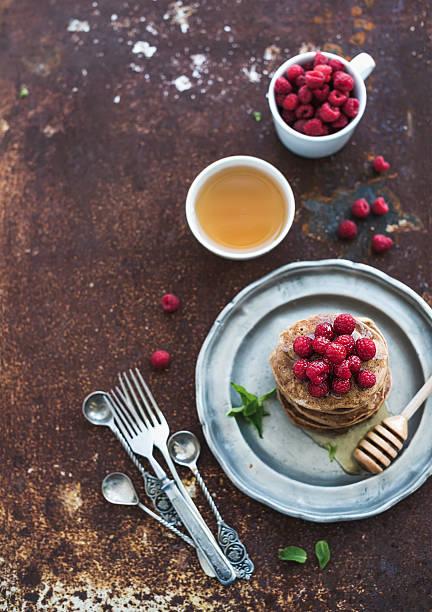 frühstück set. buchweizen-pfannkuchen mit frischen himbeeren und minze, honig - buchweizenpfannkuchen stock-fotos und bilder