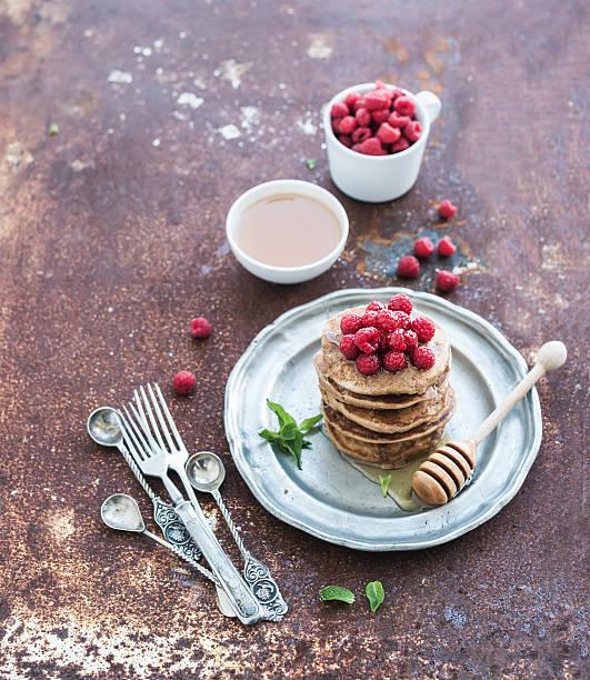 frühstück set. buchweizen-pfannkuchen mit frischen himbeeren, honig - buchweizenpfannkuchen stock-fotos und bilder