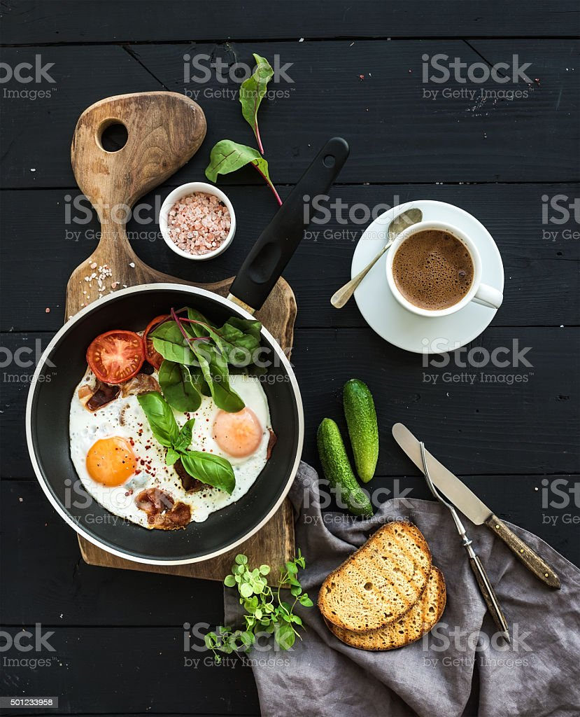 Breakfast set. Pan of fried eggs, bacon, tomatoes with bread stock photo
