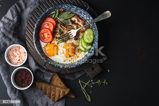 istock Breakfast set. Pan of fried eggs with bacon, fresh tomato, cucumber, sage and bread on dark serving board over black background 822169986