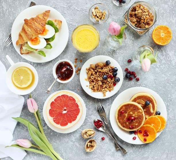 frühstücksset mit pfannkuchen, müsli, croissants sandwich, frische grapefruit orange und grüner tee. tischdekoration für festliche osterfrühstück. - brunch stock-fotos und bilder