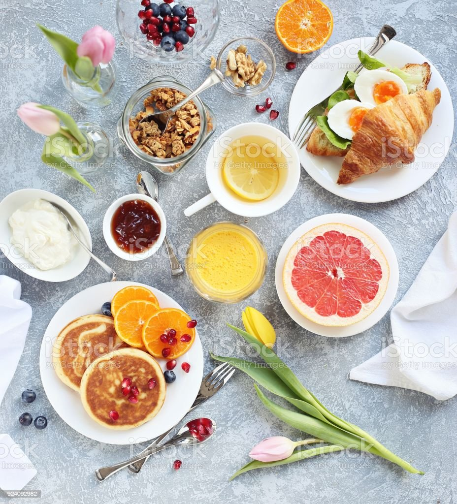 Breakfast set with pancakes, granola, croissant sandwich, grapefruit orange fresh and green tea. Table setting for festive easter breakfast. stock photo