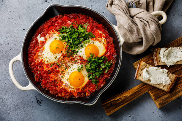 Breakfast Shakshuka Fried eggs with tomatoes in frying pan and bread with soft goat cheese