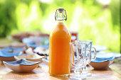 Breakfast table and glass orange juice bottle
