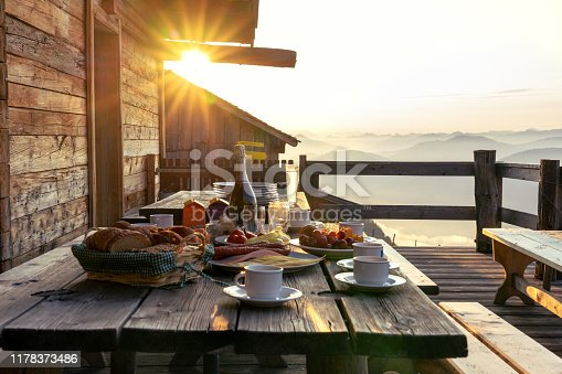 istock Breakfast table in rustic wooden terace patio of a hut hutte in Tirol alm at sunrise 1178373486