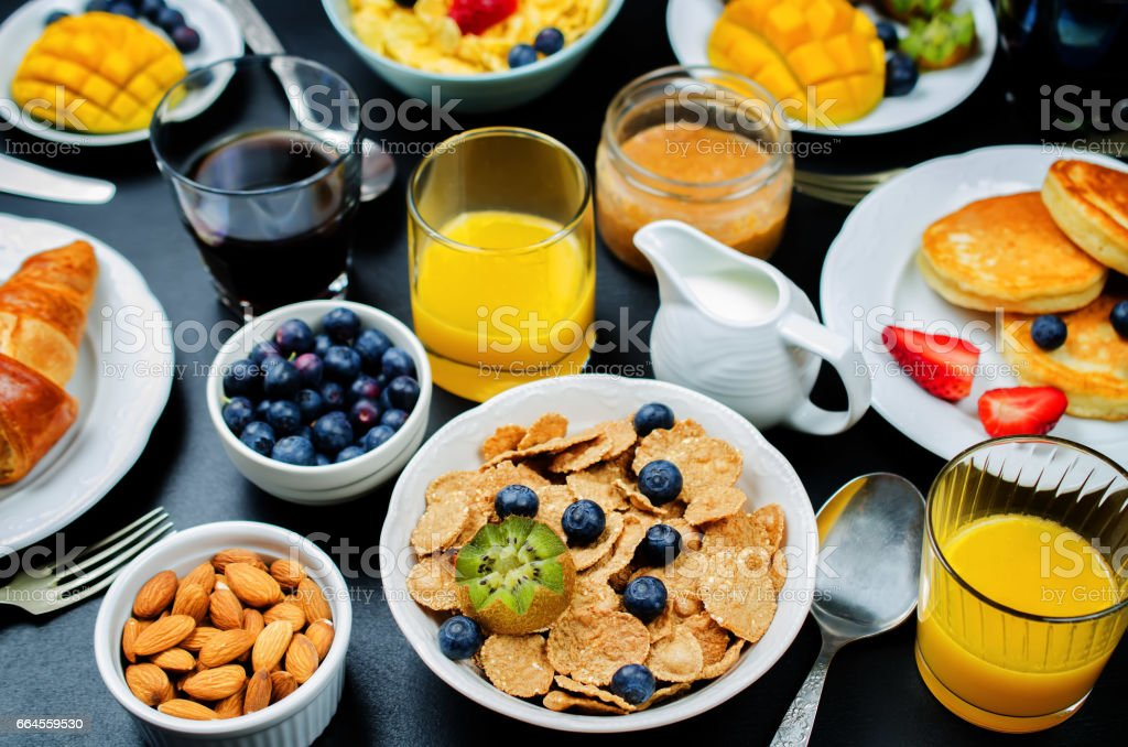 Breakfast table setting with flakes, juice, croissants, pancakes and fresh berries royalty-free stock photo