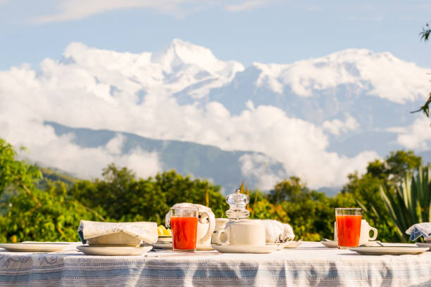 Breakfast table with coffee, tea and watermelon juice dressed in front of the Annapurna mountain range, Himalayas, Nepal. stock photo
