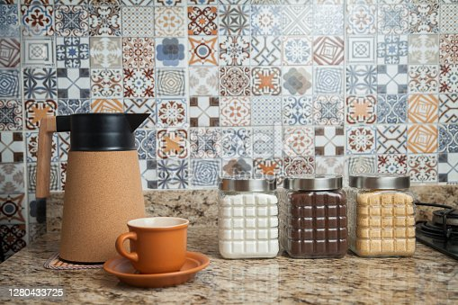 Breakfast table with coffee thermos, cup and pots of sugar, coffee and condiments. Typical Brazilian cuisine with tiles decorated in the background. Food concept. Breakfast concept.