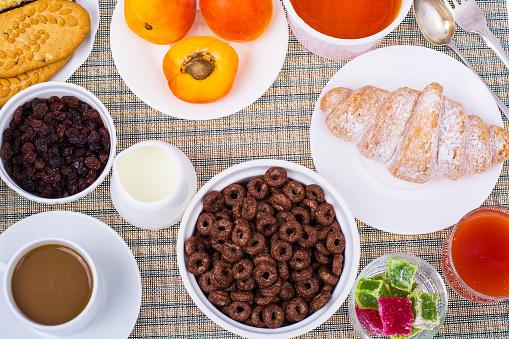 840939766 istock photo Breakfast table with croissant, muesli, milk, honey and fruits 816015220