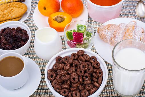 840939766 istock photo Breakfast table with croissant, muesli, milk, honey and fruits 816015262