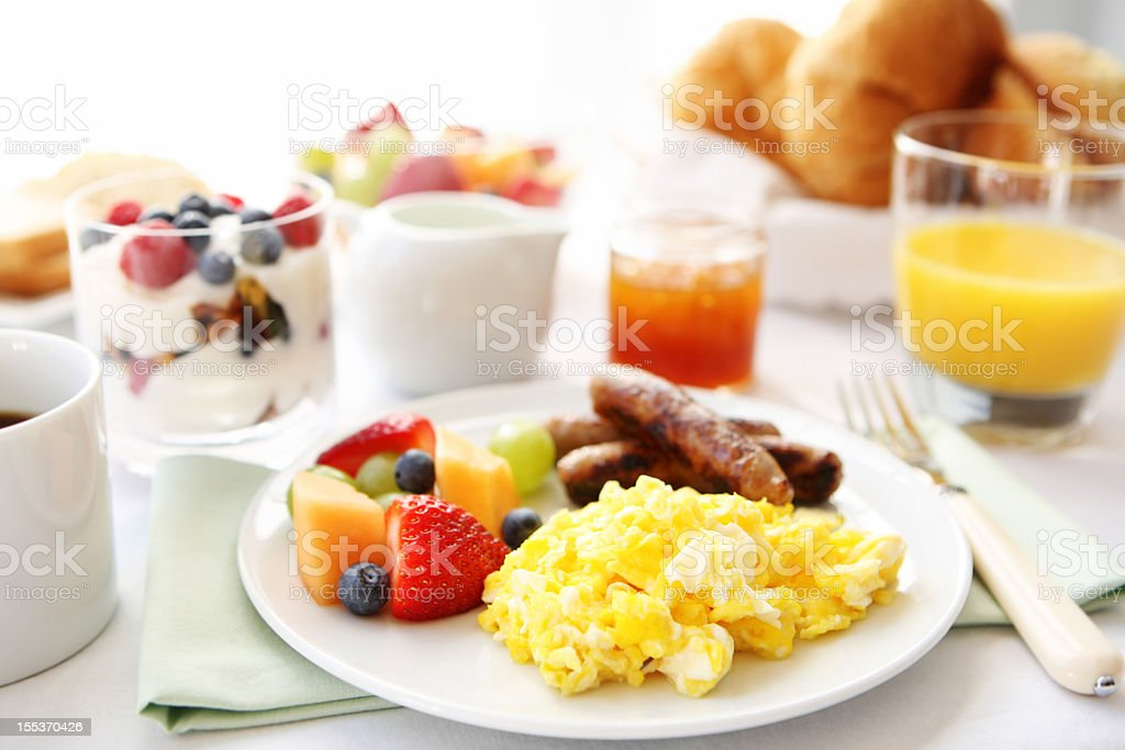 Breakfast table with eggs, fruit, and sausages stock photo