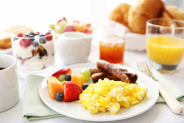 breakfast table with eggs, fruit, and sausages - ontbijt stockfoto's en -beelden