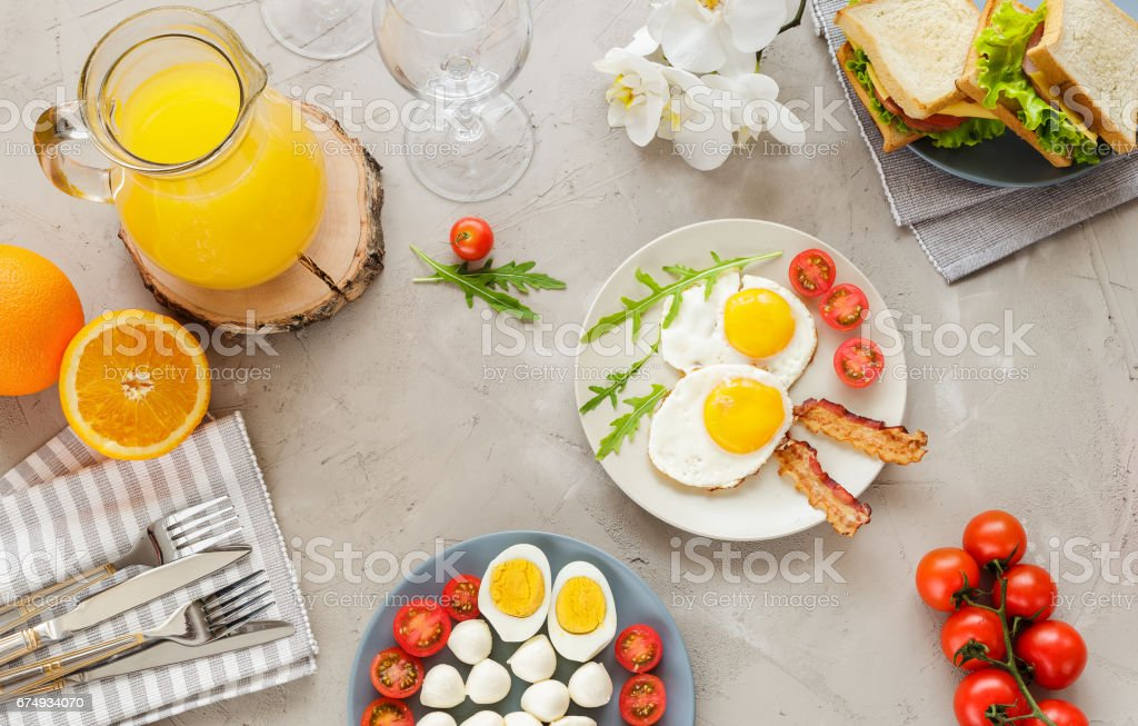 Breakfast table with fried eggs, bacon, cherry tomatoes, sanwiches royalty-free stock photo
