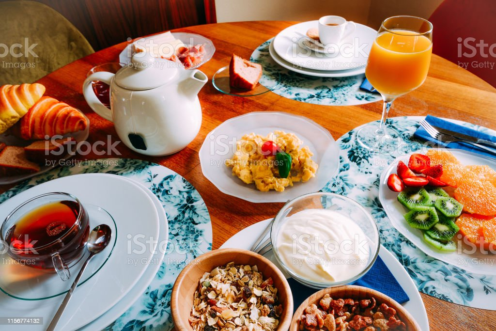 Breakfast table with variety of foods including cereals, yoghurt,...
