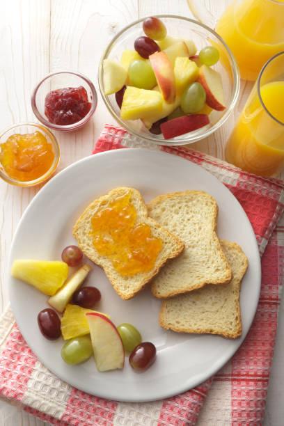 frühstück: toast, obst, salat und orangensaft stillleben - ananas marmelade stock-fotos und bilder